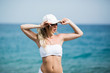Fitness girl with a perfect body is smiling near the sea