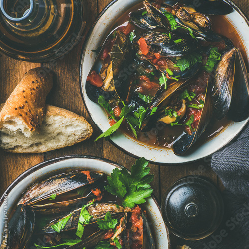 Fotografía  Belgian boiled mussels in tomato sauce with fresh parsley in serving metal bowls