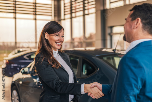 Fotografia, Obraz Cheerful car dealer handshake with customer in showroom.