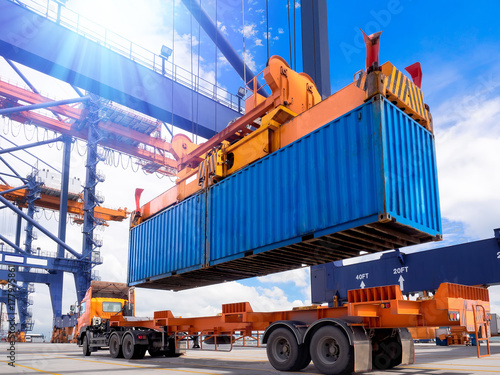 Fotografia  Industrial port crane lift up loading export containers box onboard from truck at port of Thailand,The port crane type's twinlift is the best solution for port operations