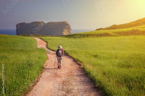Pilgrim walking towards St. Martin church on the coast of LLanes to beach of the Camaras, Asturias, Spain