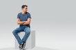Man sitting on a cube and looking away - isolated