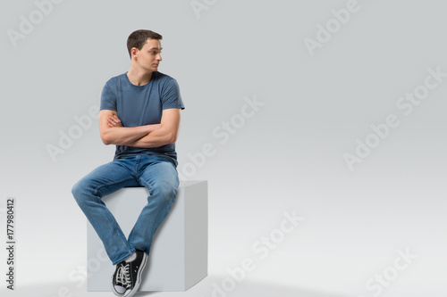 Fotografía  Man sitting on a cube and looking away - isolated