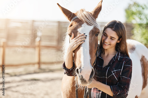 Fototapeta Young beautiful girl petting a horse taking care preparing to become a barn manager at an animal farm. obraz
