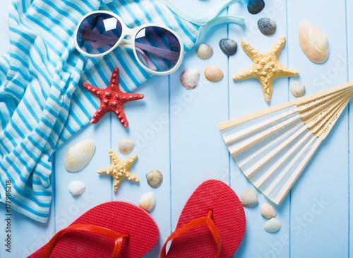 Zdjęcie XXL Akcesoria letnie dla kobiet: okulary przeciwsłoneczne, czerwone step-ins, koszula, wentylator na niebieskim tle drewna.