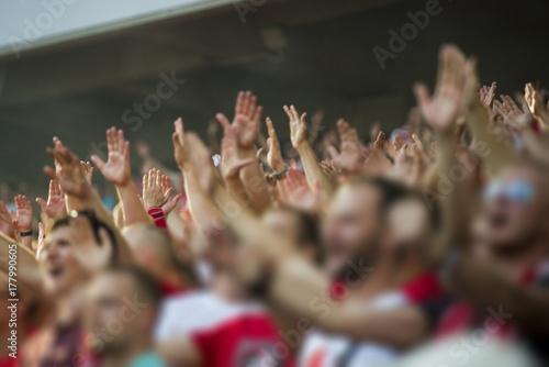 Fototapeta Football fans clapping on the podium of the stadium obraz
