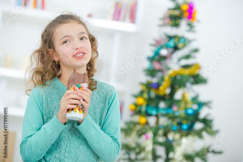Fényképezés  Young girl eating Christmas chocolate