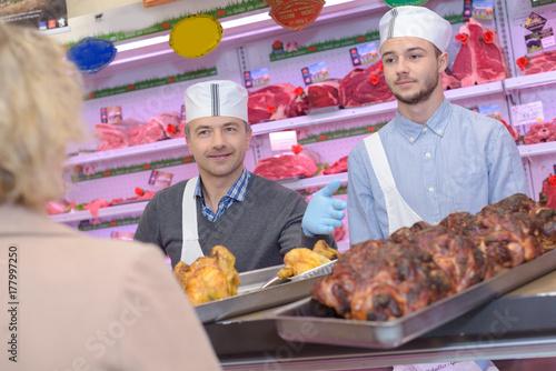 Fototapeta rzeźnik uczący młodego jak sprzedawać mięso