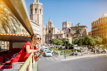 Young happy woman tourist in red dress having excursion in the open touristic bus in Valencia city, Spain