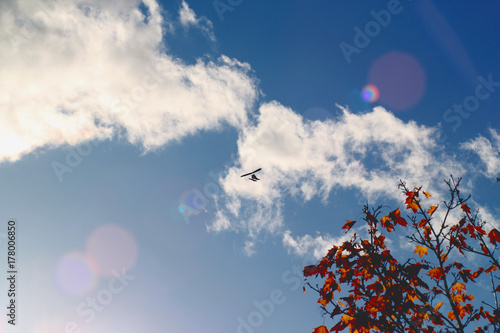 Motorized hang glider flying in the blue  cloudy sky in autumn time