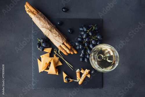 Fototapeta Cheese plate served with crackers, grapes and glass of white wine on dark background. obraz na płótnie
