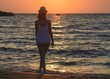 Young woman walking by the sea at sunset