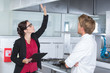 canvas print picture - woman undergoing inspection in restaurant kitchen with chef