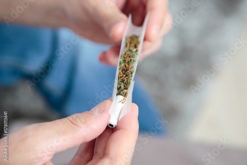 Photo  female hands rolling a joint