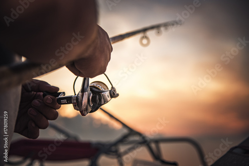 Canvas Print Fishing rod wheel closeup, man fishing with a beautiful sunrise behind him