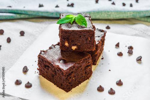 Plakat Domowej roboty ciemna czekolada i kakaowy kraciasty fudge zasycha deser z mennicą przeciw białemu tłu