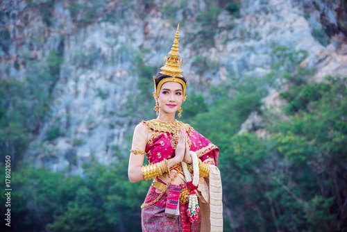 Fototapeta Beautiful asian woman in traditional Thai dress doing gesture welcome and smiles obraz