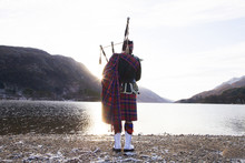 Bagpiper Playing Bagpipes By Loch, At Sunrise. Scotland.