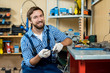 Portrait of friendly bearded mechanic wearing overall and checked shirt posing for photography with toothy smile while holding wrench in hands, interior of bicycle repair shop on background