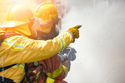 two firefighters water spray by high pressure nozzle to fire surround by smoke w Poster Mural XXL