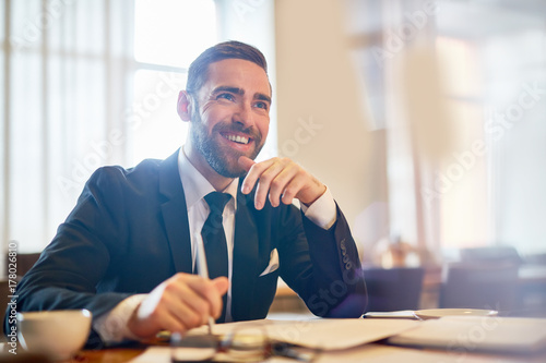 Waist-up portrait of cheerful bearded entrepreneur looking away with toothy smile while working on promising project at spacious office