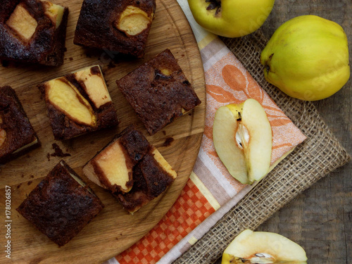 Homemade chocolate pie from corn flour with a quince on a wooden background. Gluten-free pastries. Copy space
