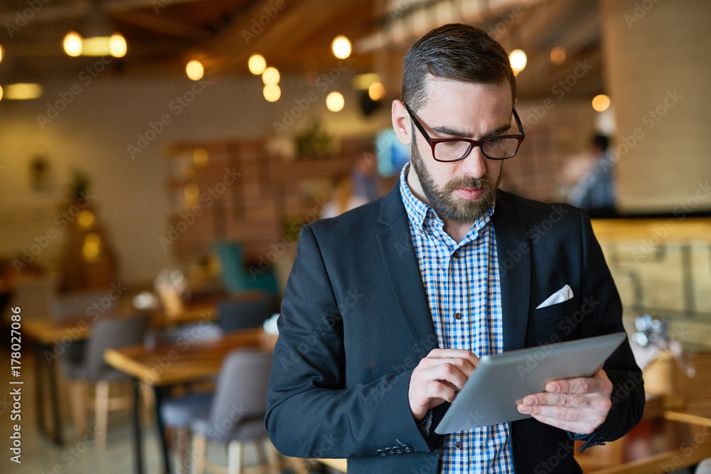 Fototapeta Waist-up portrait of concentrated bearded manager in eyeglasses checking business emails on digital tablet while standing at spacious modern restaurant