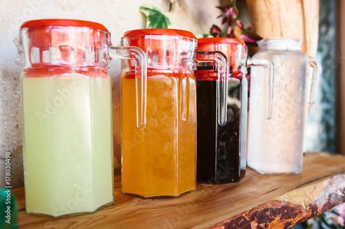 Fototapeta Na stole stoją szklane dzbanki z różnorodnymi napojami owocowymi i jagodowymi z czerwonymi pokrywkami