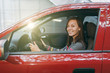 canvas print picture - Beautiful young happy smiling European brown-haired woman with healthy clean skin dressed in a striped t-shirt sits in her red car with black interior. Traveling and driving concept.