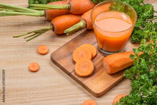 Fototapeta Szkło świeży marchwiany sok z warzywami na drewnianym stole.