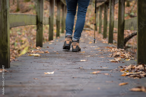Fototapeta woman walking across wooden bridge in forest in fall obraz na płótnie