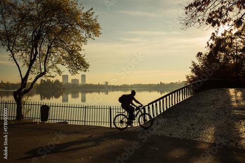 Plakat Mężczyzna jechać na rowerze w parku przy wschodem słońca z piękną jesieni colours i jezioro w tle