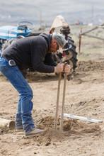 A Man Using A Post Hole Digger
