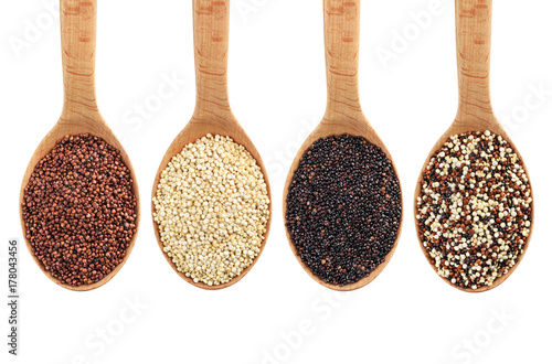Black, red and white quinoa grains on wooden spoon.