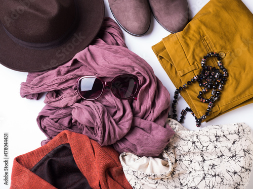Staande foto Dragen Flat lay with lady's clothes, hat, sun glasses, necklace. Autumn colours accessories on white background