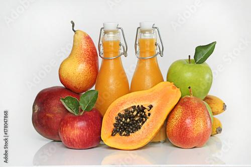 Zdjęcie XXL Mieszanka tropikalna smoothies. Pomarańczowe koktajle z mango, banan, papaja, gruszka, czerwone i zielone jabłka w przezroczystych szklanych butelkach i świeżych owoców na jasnym tle. Super jedzenie koncepcja
