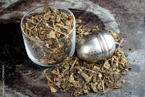 Valokuva  Green tea in and around glass jar with tea strainer.