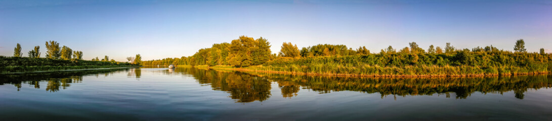 Panoramic view of a river with boat at anchor