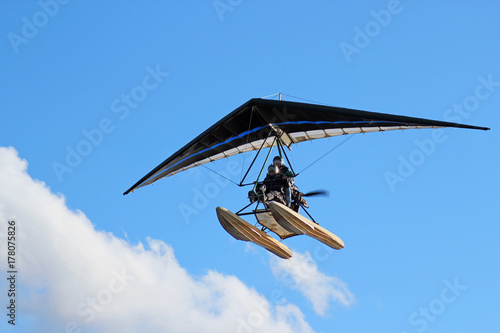 Motorized hang glider flying in the blue  cloudy sky