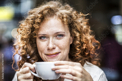 Portrait of smiling young woman with coffee cup