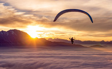 An Adventurous Sportsman Does Paragliding Above The Clouds At Sunset.