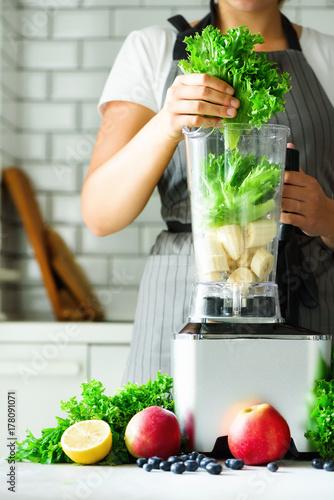 Photo  Woman blending lettuce leaves, spinach, aplles, berries, bananas