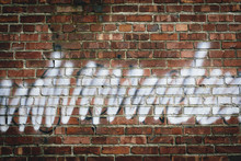 Graffiti On Brick Building Wall