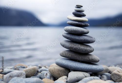 Cuadros en Lienzo Zen balancing pebbles next to a misty lake.