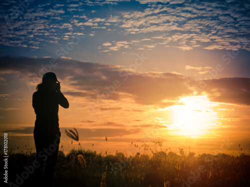 Fototapety, obrazy: Photographer taking picture at sunset