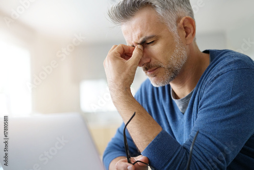 Stampa su Tela  Man at home having a headache in front of laptop