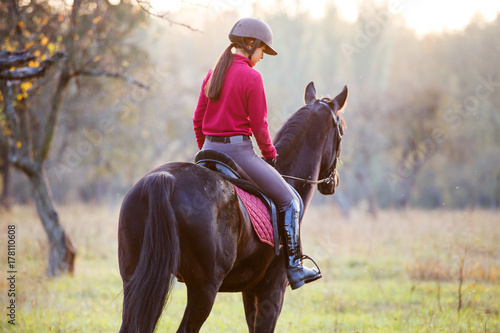 Poster Equitation Young rider girl on bay horse in the autumn park at sunset. Teenage girl riding horse in park