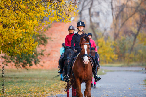 Poster Equitation Group of teenage girls riding horses in autumn park. Equestrian sport background with copy space