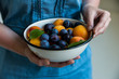 Woman holds bowl with plums and apricots