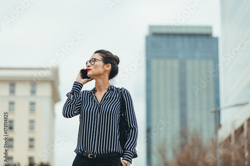 plakat Businesswoman walking outdoors with cellphone